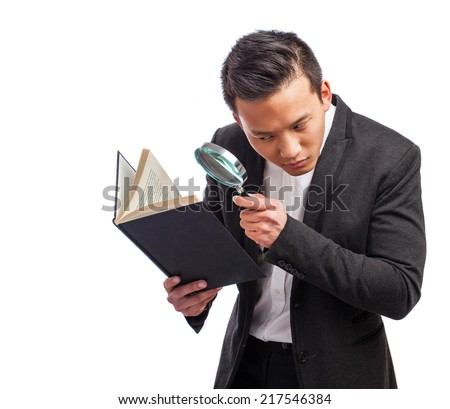 portrait of a young asian man looking a book trough a magnifying glass - stock photo