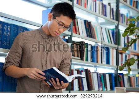 Portrait of a young asian man reading book in library  - stock photo
