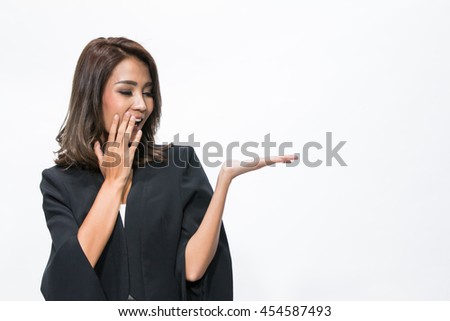 Portrait of a young asian woman in a suit, with her hand outstretched, as though she is presenting something.
