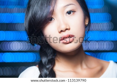 Portrait of a young Asian woman looking at camera - stock photo