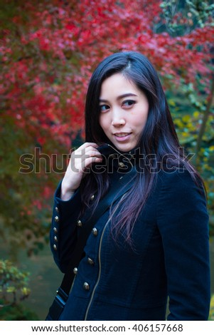 Portrait of a young Asian woman with autumn trees on the background. Happy Asian Girl in a park, Woman portrait in a park in Autumn Season