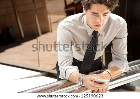 Portrait of a young aspirational businessman using a smart phone while leaning on a banister outside a modern glass office building in the city.
