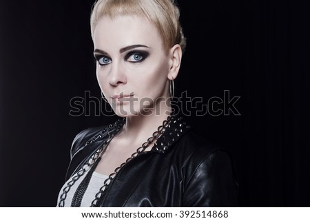 Portrait of a young attractive blonde woman in a leather jacket. She has a mohawk and a heavy dark makeup. She has large blue eyes and clear skin.