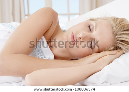Portrait of a young attractive blonde woman sleeping in bed.