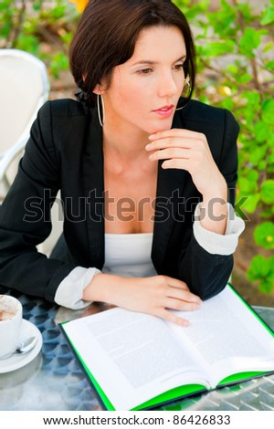 Portrait of a young attractive business woman sitting at outdoor cafe and reading book while drinking coffee - stock photo