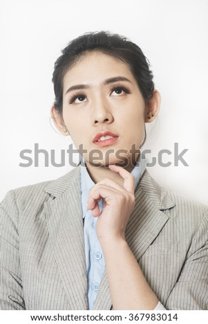 Portrait of a young attractive business woman thinking with hand on chin  - stock photo