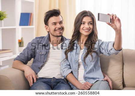 Portrait of a young attractive couple are making a selfie picture at home. - stock photo