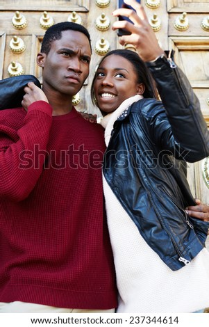 Portrait of a young attractive couple holding a smart phone and taking a self-ie self portrait of themselves fooling around, couple in love, happy couple taking self-portrait picture during travel - stock photo