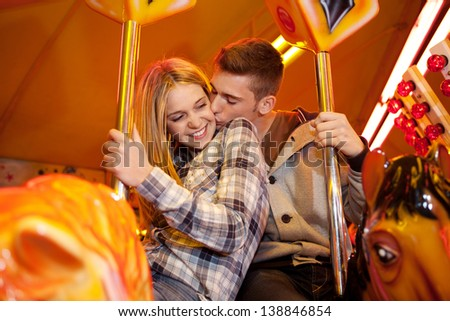 Portrait of a young attractive couple kissing and riding horses together on a colorful carousel at an amusement attractions arcade ground with multiple lights in the background at night time. - stock photo