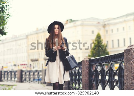 Portrait of a young attractive funky woman with long hair chatting on her mobile phone while walk on the street, beautiful hipster girl dressed in stylish clothes holding in the hands cell telephone  - stock photo