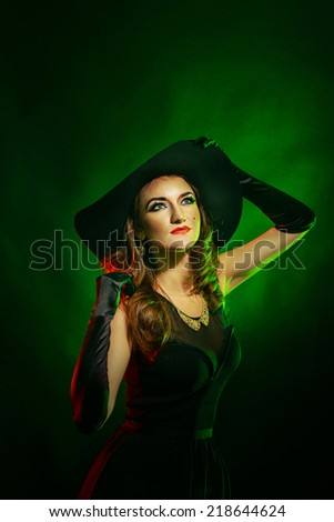 Portrait of a young attractive girl in a witch costume for Halloween - stock photo
