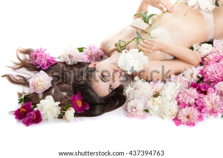 Portrait of a young attractive girl lying on the floor with flowers. Peony flowers in her hair and body. She laughs. Rest, relaxation