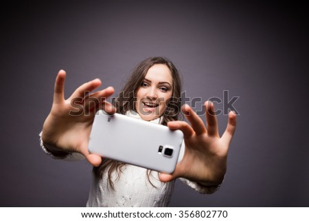 Portrait of a young attractive girl making selfie photo on smart-phone isolated on a white background - stock photo