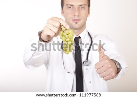 Portrait of a young attractive male doctor holding grapes and showing thumb up.