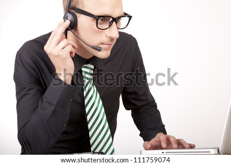 Portrait of a young attractive male receptionist with headphones. - stock photo