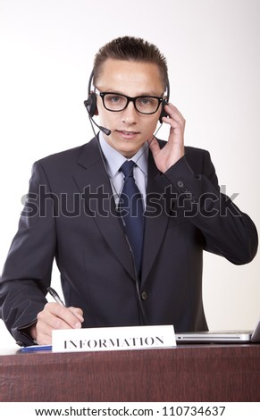 Portrait of a young attractive male receptionist working at the information desk.
