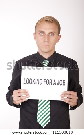 Portrait of a young attractive man holding a sign looking for a job. - stock photo