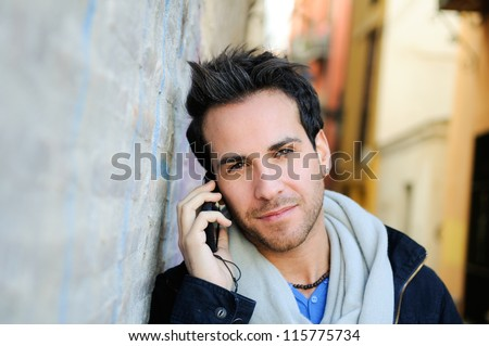 Portrait of a young attractive man in urban background talking on mobile phone - stock photo