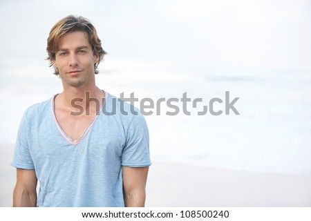 Portrait of a young attractive man on the beach with the sea in the background, smiling. - stock photo
