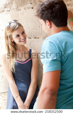 Portrait of a young attractive romantic tourist couple enjoying a day out together sightseeing, smiling against an old stone wall, outdoors. Romantic love and relationships. - stock photo