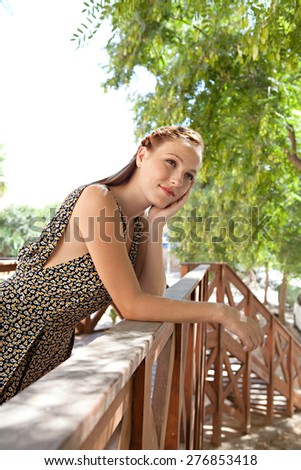 Portrait of a young attractive tourist woman leaning on a wooden banister balcony in a leafy street on holiday, smiling, exterior. Travel lifestyle vacation, outdoors park. Beautiful woman, lifestyle. - stock photo