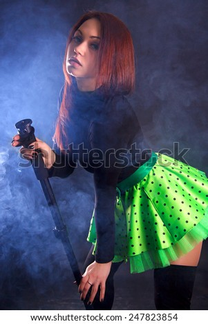 Portrait of a young attractive woman dancing with a stick over black background - stock photo