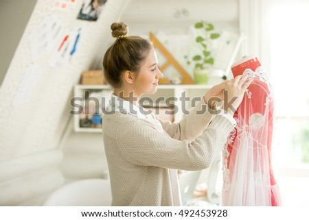 Portrait of a young attractive woman dressing a tailor dummy mannequin. Concept photo, horizontal side view
