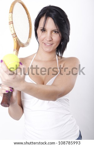 Portrait of a young attractive woman holding racket and ball.