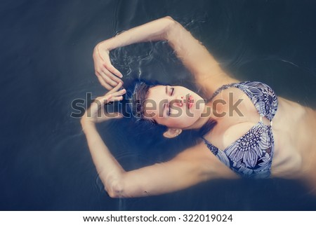 Portrait of a young attractive woman in the water - stock photo