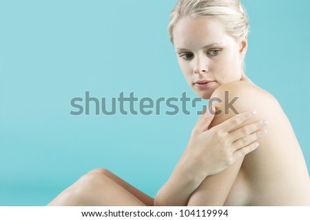 Portrait of a young attractive woman sitting down naked on a blue background. - stock photo