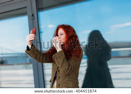 Portrait of a young attractive woman straightening red hair to making selfie photo on smartphone for Instagram - stock photo