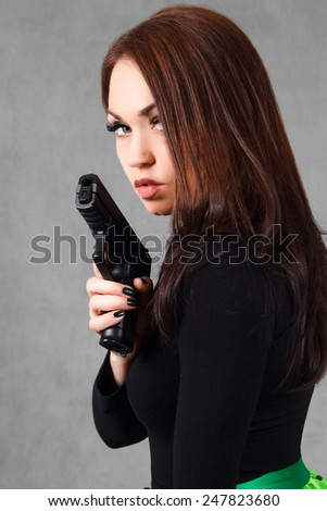 Portrait of a young attractive woman with a gun over grey background - stock photo