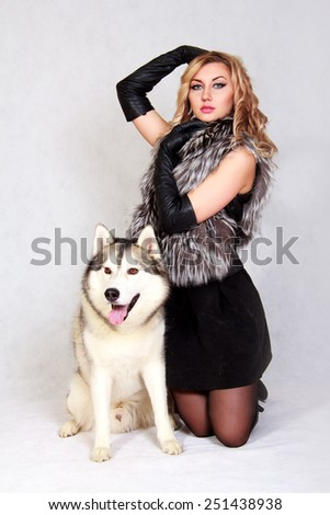 Portrait of a young attractive woman with a husky dog over grey background