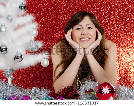 Portrait of a young attractive woman with a small christmas tree and ornaments sitting at a table in front of a red glitter background.