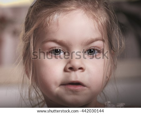 Portrait of a young baby girl with focus on the eyes, facial expression - stock photo