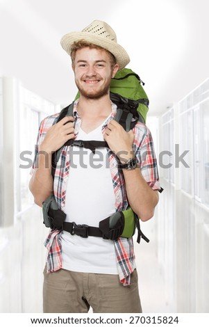 portrait of a young backpacker traveler with backpack at the airport - stock photo