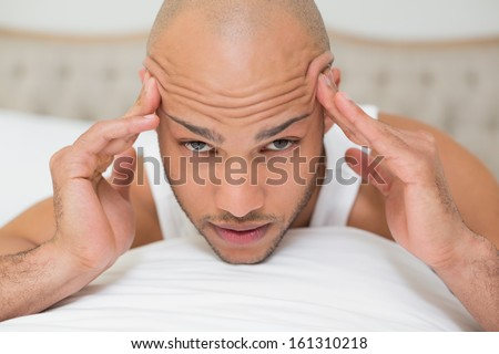 Portrait of a young bald man suffering from headache in bed at home