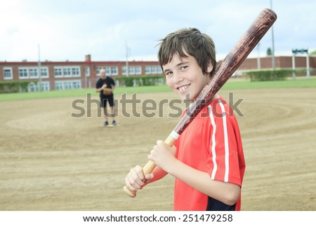 Portrait of a young baseball player in a field - stock photo