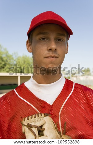 Portrait of a young baseball player with glove - stock photo