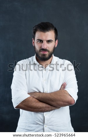 Portrait of a  young bearded man against black chalkboard