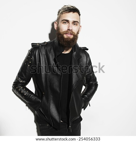 Portrait of a young bearded man in a leather jacket on a white background