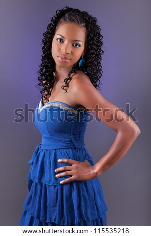 Portrait of a young beautiful african american woman in blue dress looking up - stock photo