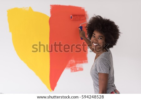 portrait of a young beautiful African American woman painting wall in her new apartment