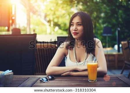 Portrait of a young beautiful asian woman enjoying sunny summer day in modern in the open air restaurant, carefree lady with copy space dreamily looking away during lunch in cozy restaurant outdoors  - stock photo
