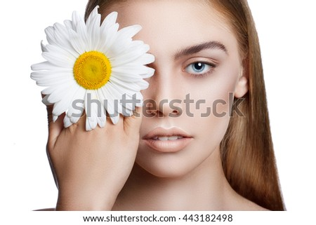 Portrait of a young beautiful blue-eyed girl with a flower. A girl holding a daisy in his hand and closes her own eyes. Close-up, blue eyes, blond hair, perfect skin, lovely make-up - stock photo