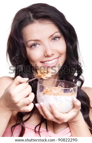 portrait of a young beautiful brunette woman eating  cornflakes with milk, isolated against white background