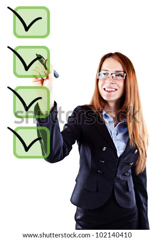 Portrait of a young beautiful  business woman checking on checklist boxes - stock photo