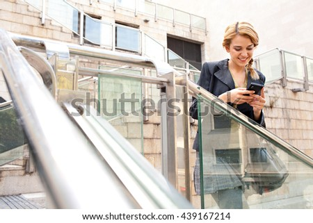 Portrait of a young beautiful business woman holding and using a smart phone in slick stairs in financial city, sunny outdoors. Professional girl using technology, smiling. Lifestyle in exterior. - stock photo