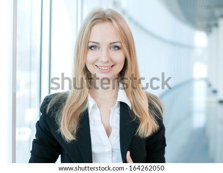 Portrait of a young beautiful business woman smiling at office building - stock photo