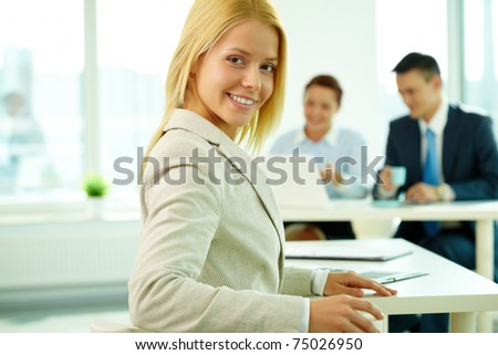 Portrait of a young beautiful businesswoman in working environment
